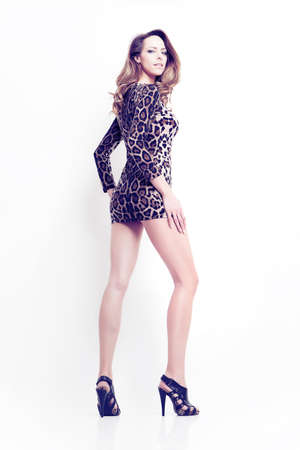 attractive brunette girl pose in animal skin clothes, long leg Stock Photo