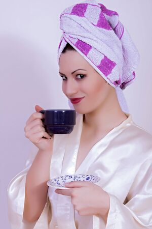 breakfast smiley face: portrait of woman with towel on her head drinking coffee Stock Photo