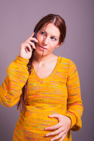 portrait of pregnant woman talking on cell phone photo