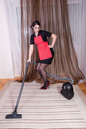 portrait of attractive housewife with vacuum cleaner photo