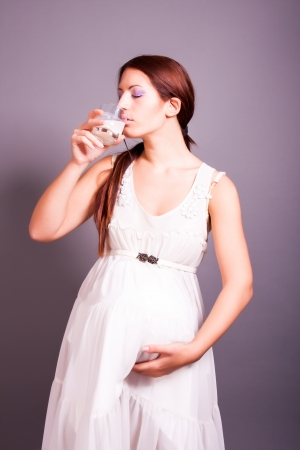 portrait of pregnant woman drinking milk photo