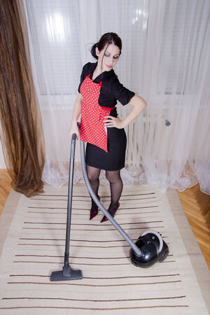 keeping room: portrait of attractive housewife with vacuum cleaner