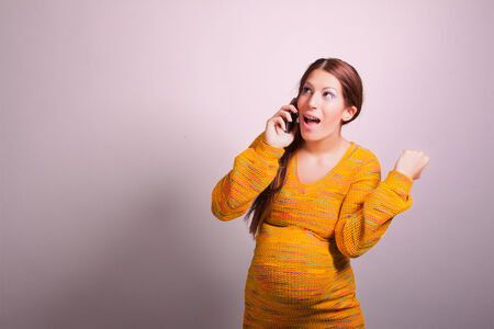 portrait of pregnant woman using cell phone photo