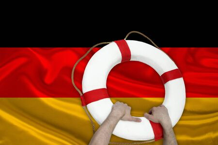 male hands hold on to a white lifebuoy against the background of the silk national flag of Germany, the concept of medical insurance, tourism, disaster, humanitarian aid