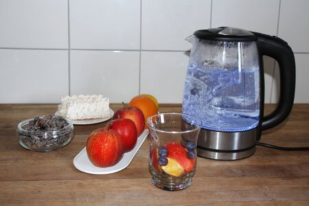 teapot boils water for making tea, a glass cup with sliced ??apples, berries, hawthorn flowers, fruits in the background, the concept of a healthy diet, vitamin breakfast