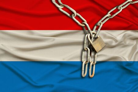 iron chain and lock on the silk national flag of Luxembourg with beautiful folds, the concept of a ban on tourism, political repression, crime, violation of the rights and freedoms of citizens