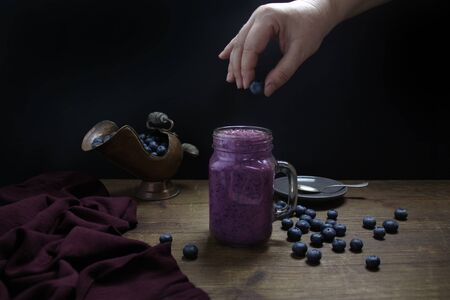 girl throws berries into mason jar mug filled with healthy blueberry smoothie, linen napkin, copper jug, healthy eating concept 免版税图像