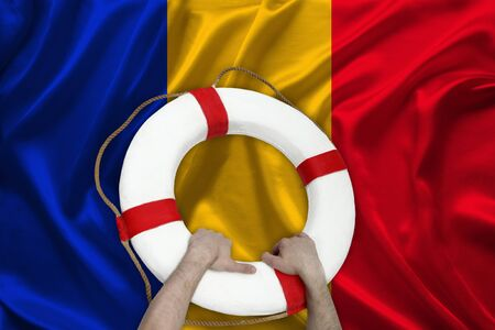 male hands hold on a white lifebuoy against the background of the silk national flag of Romania, the concept of medical insurance, tourism, disaster, humanitarian assistance