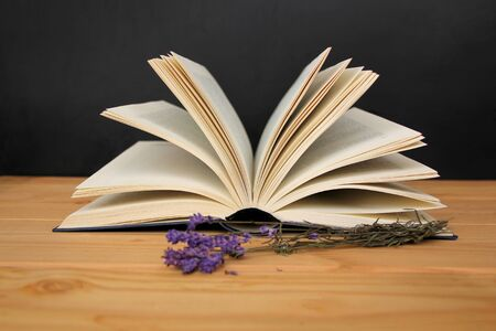 open paper book with open pages, reading concept, on a wooden table, next to a sprig of lilac lavender, horizontal, closeup, copy space