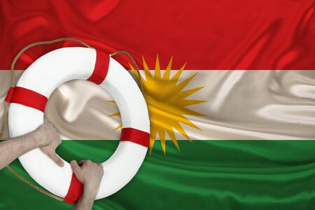 male hands hold on a white lifebuoy against the background of the silk national flag of the country of Kurdistan, rojava, the concept of medical insurance, tourism, disaster, humanitarian aid