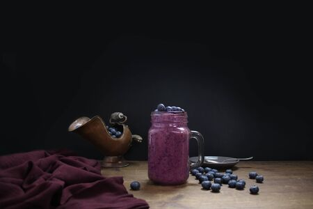 mason jar mug filled with healthy smoothies made from blueberries, linen napkin, copper jug, healthy eating concept 免版税图像