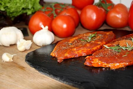 juicy raw meat marinated with spices on a black board, steaks with rosemary, red tomatoes, paprika, garlic, dill, concept of protein nutrition, diet, barbecue party, cooking homemade food