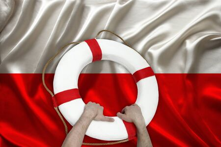 male hands hold on a white lifebuoy against the background of the silk national flag of Poland, the concept of medical insurance, tourism, disaster, humanitarian aid