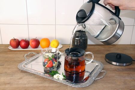 man holds a kettle with boiling water in his hands, makes tea, a glass cup with sliced apples, berries, hawthorn flowers, fruits in the background, the concept of a healthy diet, vitamin breakfast