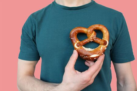 beautiful freshly baked pretzel, heart, German national dish with a golden brown crust in a male hand close-up, the concept of traditional Hesse cuisine, organic food