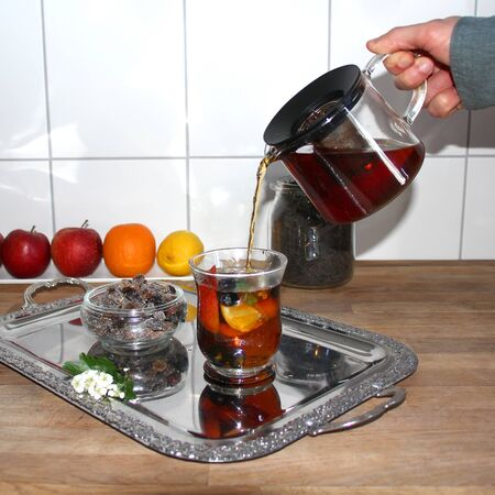 man holds a teapot with tea leaves in his hands, pours it into a glass cup with slices of apples, berries, hawthorn flowers, fruits in the background, the concept of a healthy diet, vitamin breakfast