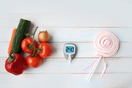 blood glucose meter, a medical device for measuring blood glucose, vegetables, tomatoes, cucumber, carrots, onions, paprika and sweet marshmallow on a stick, the concept of a healthy diet, diet choice