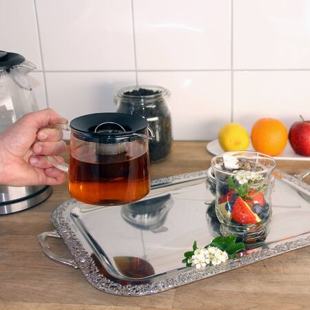 man holds in his hands a teapot with tea leaves, in the background fruits, a glass cup with sliced apples, berries, hawthorn flowers, the concept of a healthy diet, diet, vitamin breakfast Zdjęcie Seryjne
