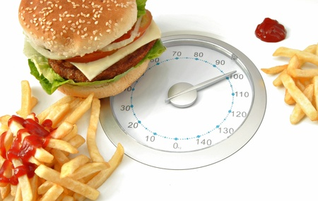 Scales on one side with hamburger and fries with ketchup on the other hand Stock Photo - 9770194