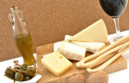 Still made ​​up of different types of cheese, a glass of wine back and forth even a bottle of olive oil with some capers photo