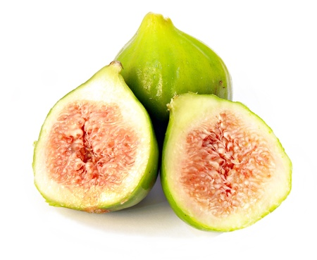 Two figs, one cut in half, surrounded by white photo