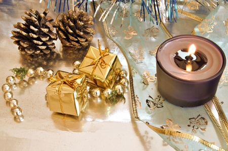 Christmas gift boxes with pineapple, pearls and a lighted candle on a bright background photo