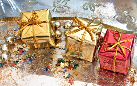 Christmas gift boxes with beads and glitter on a bright background Stock Photo