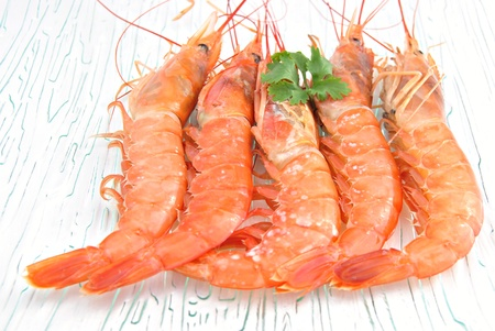 incommunicado: Five prawns stacked side by side on transparent glass plate