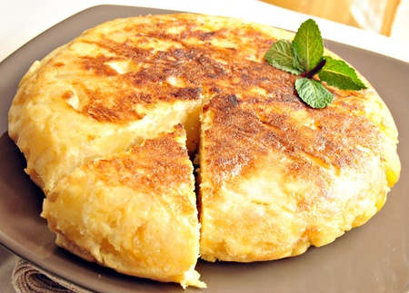 spanish food: Omelette which has been cut off a piece, decorated with a green leaf