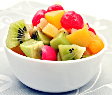 Fruit salad made up of cherries, kiwi and peaches in a bowl