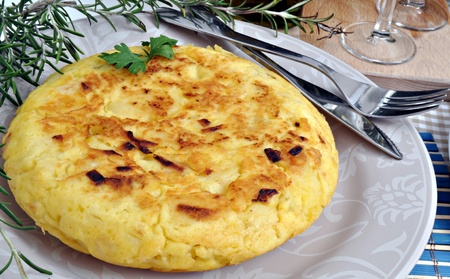 omelette: Spanish Potato omelette decorated with branches of rosemary served on a plate Stock Photo