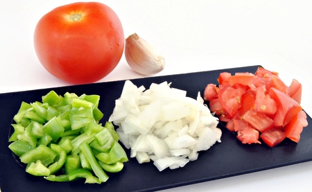 Pepper, tomato and onion, cut into pieces on a black plate, is a tomato and a garlic clove in the background Stock Photo - 10753955