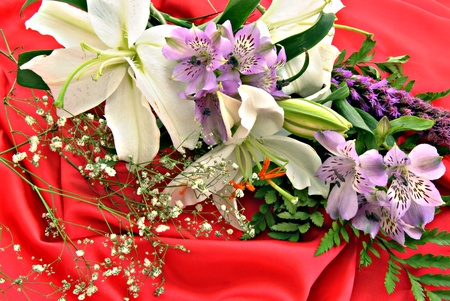 Several flowers of different colors on red satin cloth photo