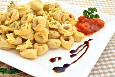 Tortellini served in a square plate decorated with parsley and tomato sauce on the side