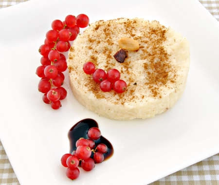 Rice pudding with cinnamon on top, next is caramel with currants photo