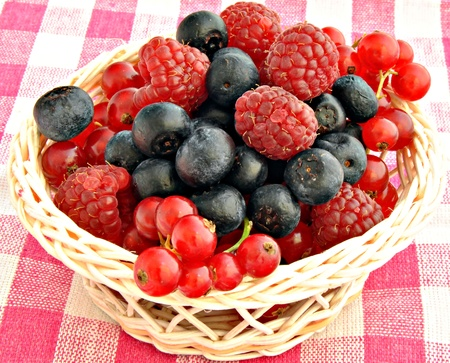 Blackberries blueberries and currants in a glass jar in a wicker basket on a tablecloth photo