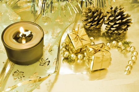 Two gift boxes on a yellow background with pine cones and candle photo