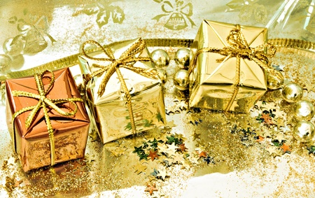 Three gift boxes on yellow background, with confetti and beads photo