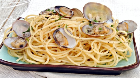 Sphaguetti with clams served on blue rectangular plate of rustic wood background photo