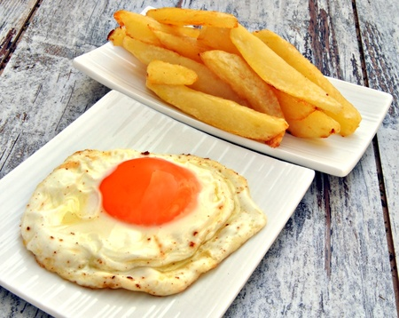 Egg and chips served in different dishes rustic background Stock Photo - 11085052