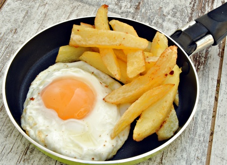 Fried egg with potatoes, served in a pan, rustic background Stock Photo - 11085056