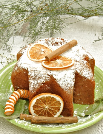 Panneton decorated with orange slices and cinnamon, with sugar on top, rustic background photo