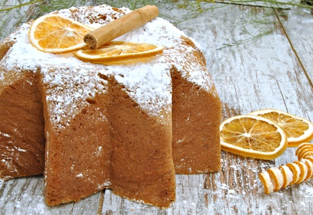 Panneton decorated with orange slices and cinnamon, with sugar on top, rustic background