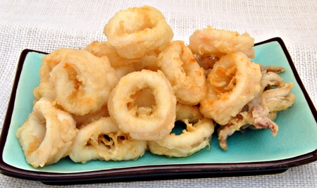 Fried calamari, rectangular plate placed on a blue background, surrounded by a cloth