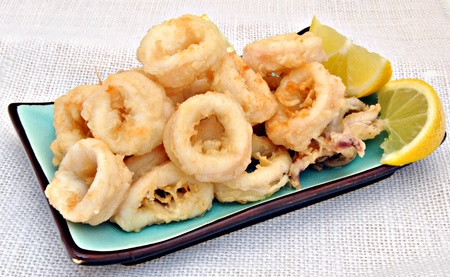 Fried calamari, rectangular plate placed on a blue background, surrounded by a cloth photo