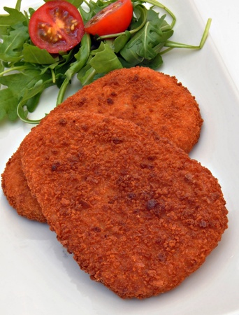 two breaded steak alongside a salad of arugula photo