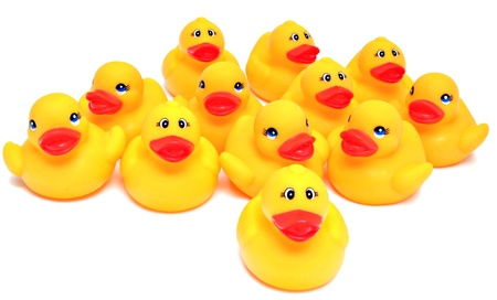 Group of yellow rubber ducks next to each other surrounded by white background