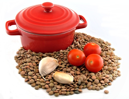 Casserole with raw lentils, tomato, garlic and onion, surrounded by white background photo