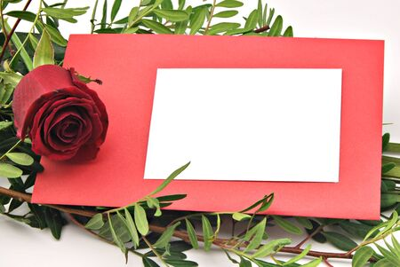 White card on red card with a rose surrounded by leafy branches