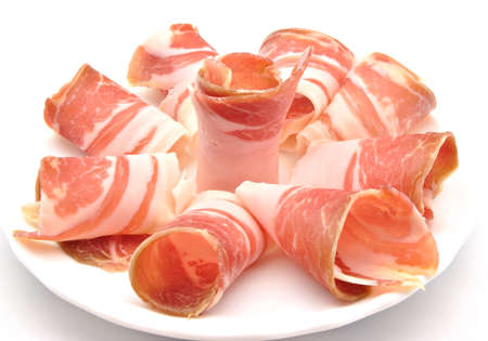 Serrano ham slices next to each other, surrounded by white background photo